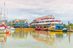 View from Fisherman`s Wharf of docks, restaurants, and tourists preparing to go on whale watching tour royalty free stock image