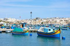 View of the fishing harbour, Marsaxlokk, Malta. Traditional Maltese Dghajsa fishing boats in the harbour with waterfront buildings to the rear, Marsaxlokk Stock Photos