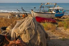 A view of a fishing net in front of the boat on the beach. Beautiful calm sea and water during an hot summer day.  royalty free stock photo