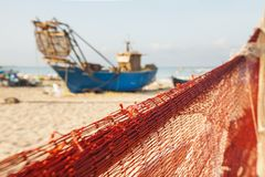 A view of a fishing net in front of the boat on the beach. Beautiful calm sea and water during an hot summer day.  royalty free stock images