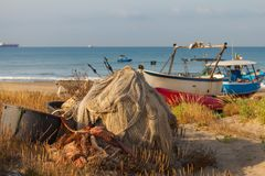 A view of a fishing net in front of the boat on the beach. Beautiful calm sea and water during an hot summer day.  royalty free stock photography