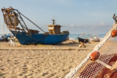 A view of a fishing net in front of the boat on the beach. Beautiful calm sea and water during an hot summer day.  stock photography