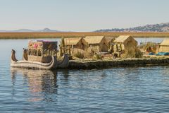 View of floating island Uros, Lake Titicaca, Peru, Bolivia. And reed boat with its reflection Stock Photos