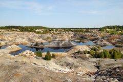 Flooded quarry with lakes and dried hills with rare vegetation. stock photography