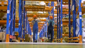 A low view on two warehouse inspectors walking away. stock video footage