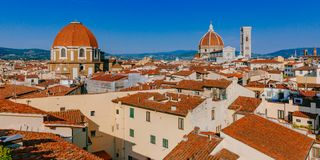 Florence Cathedral, Giotto`s Bell Tower, and San Lorenzo Basilica under blue sky, over houses of the historical center of Florenc stock images