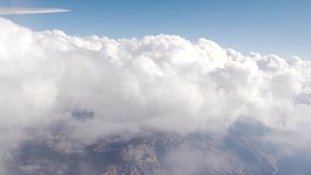 View of flying above white clouds with mountains below on commercial flight to Las Vegas USA. With Wing. Mid Flight, United States - April 19, 2019: View of stock footage