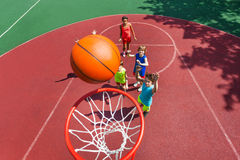 View of flying ball to basket from top, teens play Royalty Free Stock Photos
