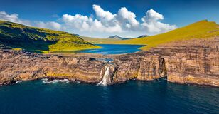 View from flying drone. Panoramic morning view of Bosdalafossur waterfall, that falls directly into the ocean. Exciting summer sce