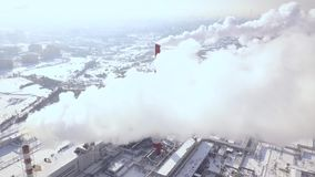 View from flying drone smoke clouds from boiler pipes on heating plant in city. Smoking chimney on power plant in modern. City aerial view. Smoke emission from stock footage