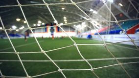 View through focused net. Blurred players play on stock footage
