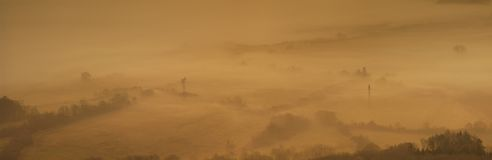 View into foggy countryside within early morning. Stock Image