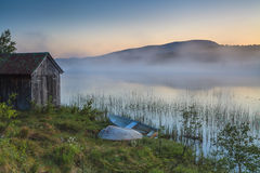 View on foggy lake with boats on the shore. Stock Images