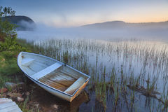 View on foggy lake with boats on the shore. stock photography