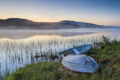 View on foggy lake with boats on the shore. Royalty Free Stock Photo