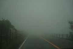 View of foggy roadway and fence while driving through local road on rainy and bad weather day on mount Aso area Stock Photos
