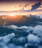 View of the foggy Val di Fassa valley with passo Sella. National Stock Photos
