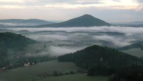 View into foggy valley below view point in Bohemian Saxony Switzerland. The fog is moving between hills stock video footage