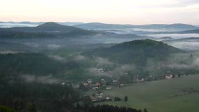 View into foggy valley below view point in Bohemian Saxony Switzerland. The fog is moving between hills Royalty Free Stock Photo