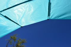 View from foldable sunshield on summer blue sky and beach tree in left corner. Image taken during summer vacation season Royalty Free Stock Image