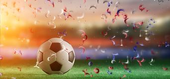Football ball on the field of a world cup stadium with streamer. View of a Football ball on the field of a world cup stadium with streamers - 3d rendering royalty free stock image