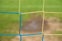 View from football gate to water and mude in poor soccer field. Damaged lawn in outdoor football stadium Royalty Free Stock Photo