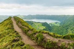 View of a footpath at the Miradouro da Grota do Inferno viewpoint leading towards one of the crater lakes at Sete Cidades