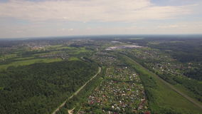 View of forest, country houses against blue sky with clouds at summer, Moscow, Russia. Aerial high level flight above the countryside in Russia. View of forest stock footage
