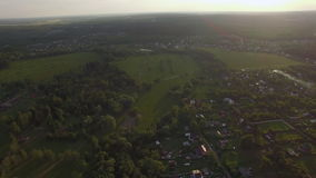 View of forest, country houses against blue sky with clouds in sunset at summer, Russia. Aerial high level flight above the countryside in Russia. View of forest stock footage