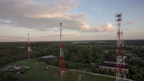 View of forest, country houses and base stations against blue sky with clouds in daylight at summer, Russia. Aerial flight above the countryside in Russia. View stock footage