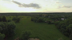 View of forest, lake and country houses against blue sky with sun and clouds in sunset at summer, Russia. Aerial flight above the countryside in Russia. View of stock video footage