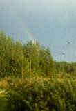 View of forest and rainbow through window. With drops Royalty Free Stock Photography