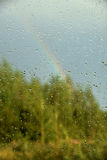 View of forest and rainbow through window. With drops Stock Image