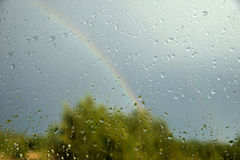 View of forest and rainbow through window. With drops Royalty Free Stock Photo