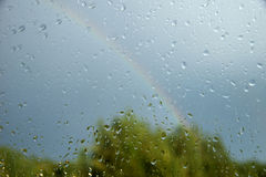 View of forest and rainbow through window. With drops Royalty Free Stock Image