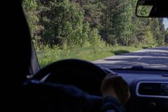 View of the forest road from the front window of the car. Driver`s hand holding the steering wheel, in defocus. stock photos