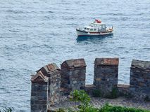 View from the fortress wall of a small boat on the sea surface. Part of the tower of the famous castle Rumeli Hisari on the Bospho royalty free stock images