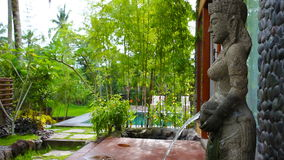 View of fountain with ancient, Hindu sculpture in garden stock footage