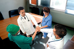 View of four Doctors putting their hands together. Royalty Free Stock Photos