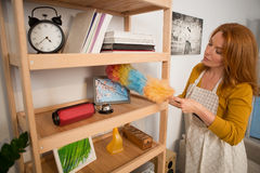 View of foxy woman using whisk to clean shelves from dust. Housewife doing cleanup in the room Stock Photo