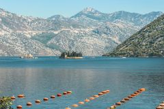 View of a fragment of an oyster farm on the background of the mountains and the island of Gospa with a small church . royalty free stock photography