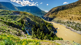 View of the Fraser River as it flows to the town of Lillooet. In the Chilcotin region on British Columbia. A small waterfall tumbling down into the river royalty free stock images