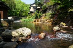 View of fresh river stream flow, stone bank and natural rock cascade with green trees and local buildings in Kurokawa onsen town. Japan Royalty Free Stock Photos