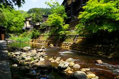 View of fresh river stream, stone bank and natural rock beach with green trees and local buildings in Kurokawa onsen town. Japan Royalty Free Stock Photo