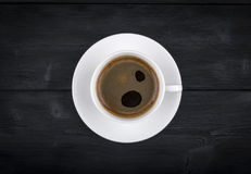 View of a freshly brewed mug of espresso coffee on rustic wooden background with woodgrain texture. Coffee break style, concept. Royalty Free Stock Image