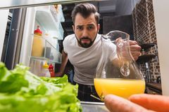View from fridge at man. Taking out jug of juice royalty free stock images