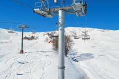 Free View From A Moving Ski Chair Lift In Winter, High Above The Ground, In Les Sybelles Ski Domain, France, On A Day With Perfect Sky Royalty Free Stock Photo - 168880355