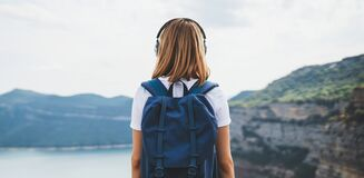 Free View From Behind Girl With Blonde Hair Listening To Music On Headphones Standing High In Rocky Mountains Enjoying View River Royalty Free Stock Photography - 191452747