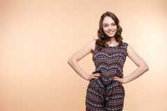 View from front of beautiful slim woman standing steady. On frey isolated background. Young looking at camera, smiling and posing in studio stock photo