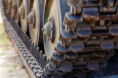 Close-up of a tank caterpillar howitzer caterpillars with wheeled rollers of a heavy tank. View of the front of the caterpillar tank standing on the ground with royalty free stock photo